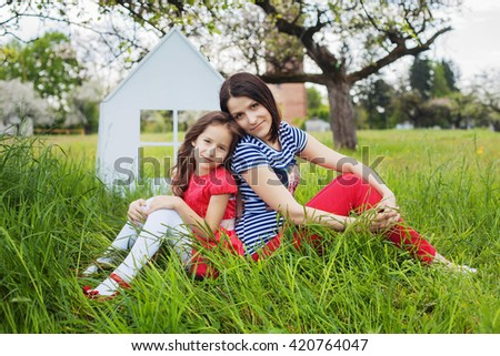 happy mother with a beautiful daughter in the garden