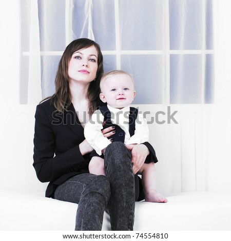 happy mother with a child at home on white sofa - stock photo