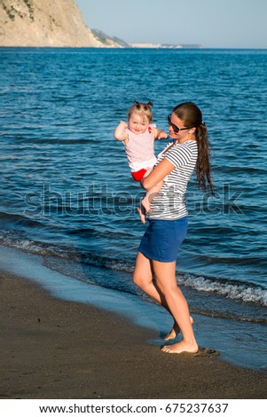 Happy mother with a small girl walking on a beach. Zakynthos, Greece. Ionic Sea