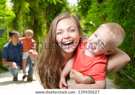 happy mother with a son on the background of his husband with a second child