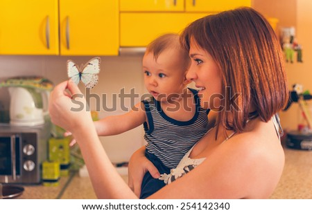 Happy Mother With Adorable Baby Boy Looking Butterfly Toy - stock photo