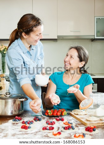 Happy mother with adult daughter  making berries dumplings at home