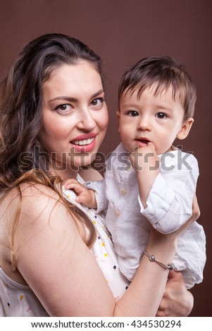 Happy mother with baby child. Holding her son in hand in studio photo on brown background - stock photo