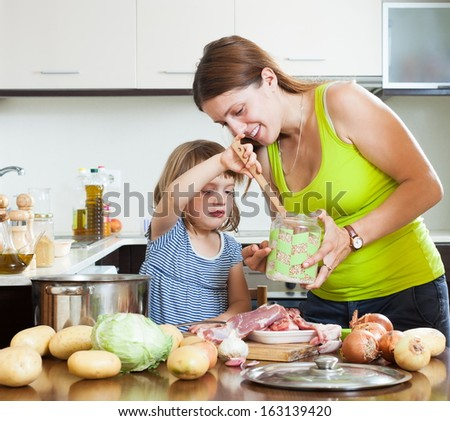 Happy mother with baby cooking with meat and vegetables - stock photo