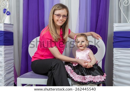 Happy mother with  baby daughter in a beautiful dress at home near the fireplace. Happy smiling - stock photo