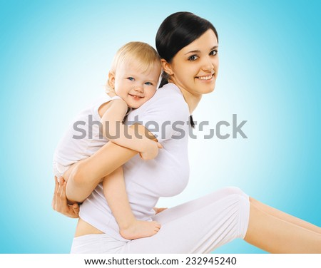 Happy mother with baby doing exercise - gymnastics, yoga, fitness and health concept - stock photo