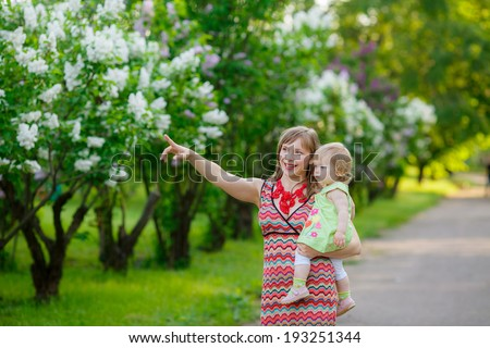happy mother with baby garden of blooming lilacs. Mom throws baby. communication with the child mom. happiness. family