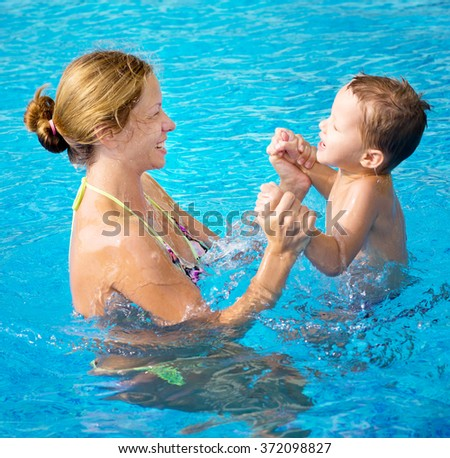 happy mother with baby in swimming pool