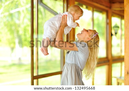 Happy mother with baby outdoors - stock photo