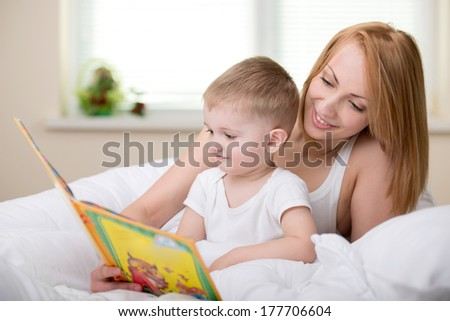 Happy mother with baby reading book - stock photo