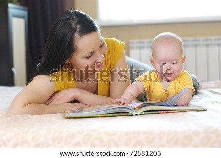 happy mother with baby reading book