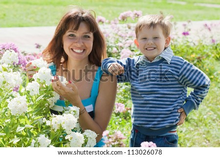 Happy mother with boy in phlox plant at garden