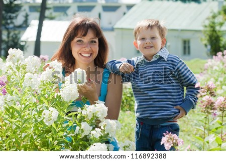 Happy mother with boy in phlox plant at garden - stock photo