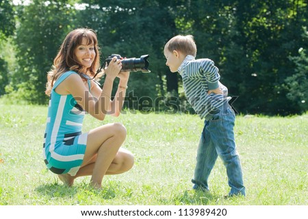 Happy mother with boy taking photo on grass in park - stock photo
