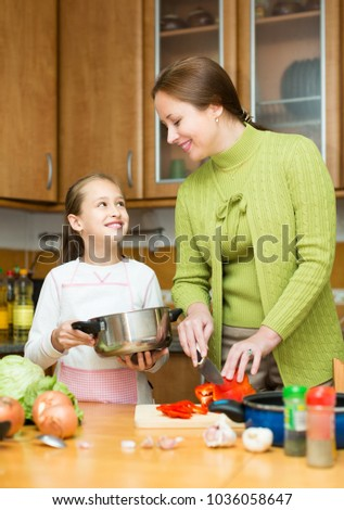 Happy mother with cheerful little daughter cooking together at home kitchen and smiling