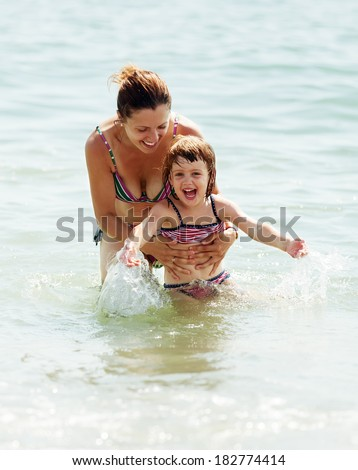 Happy mother with child in sea
