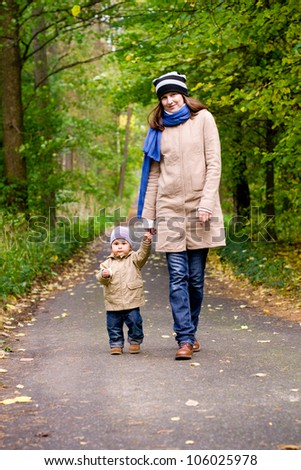 Happy mother with child walking in autumn park - stock photo