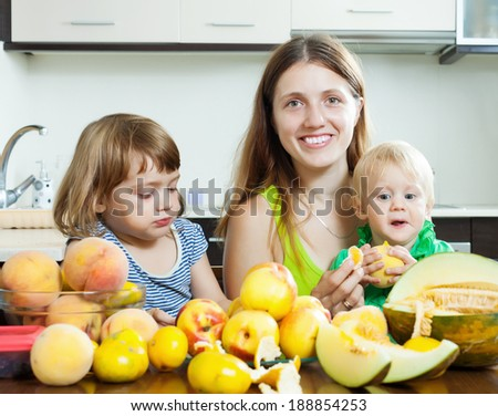 Happy mother with children eating melon and other fruits over  table at home
