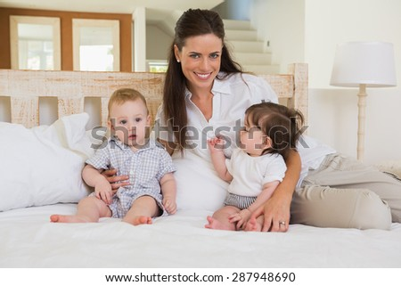 Happy mother with cute babies boy and girl at home in bedroom - stock photo