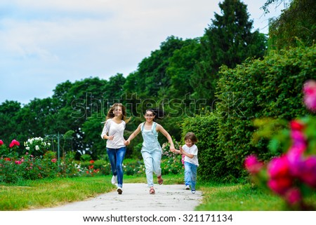 Happy Mother with daughter and son running on grass smiling
