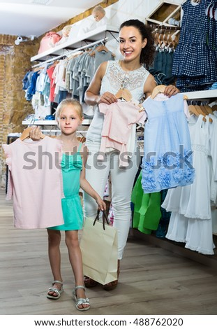 happy mother with daughter buying kids clothes in shop