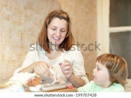 Happy mother with daughter cooking in foil at kitchen. Focus on woman - stock photo