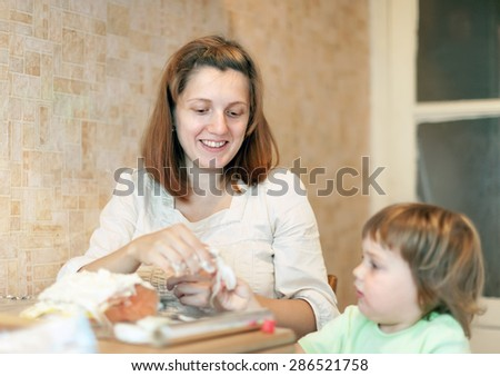 Happy mother with daughter cooking salmon in foil at kitchen. Focus on woman - stock photo