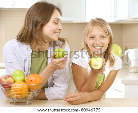 Happy Mother with Daughter eating Healthy food. Kitchen. Healthy Eating Concept - stock photo