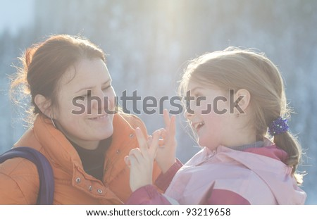 Happy mother with daughter in winter