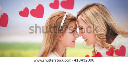 Happy mother with daughter looking each other against white background against nature scene - stock photo