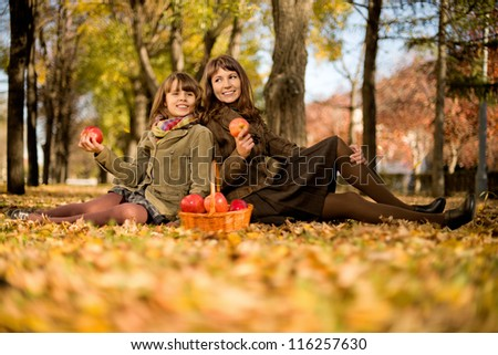 happy mother with daughter sit on autumnal  leaf and eat apple - stock photo