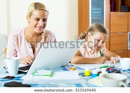 Happy mother with daughter working from home using laptop - stock photo