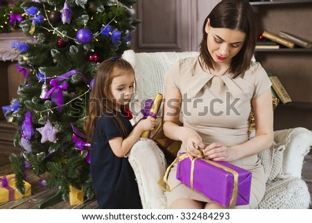 Happy mother with daughter wrapping Christmas gifts at home near the Christmas tree