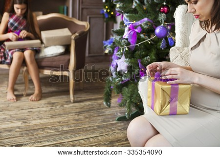 Happy mother with daughter wrapping Christmas gifts at home near the Christmas tree. Close up