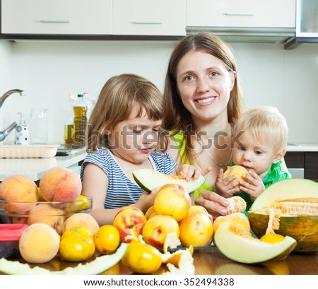 Happy mother with daughters eating melon and peaches over table at home interior