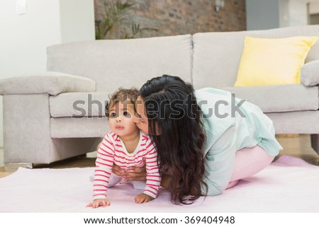 Happy mother with her baby daughter on the carpet in living room - stock photo