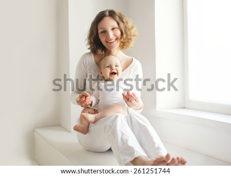 Happy mother with her baby having fun together at home in white room near window - stock photo