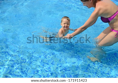 happy mother with her baby in the swimming pool