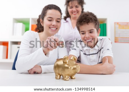 Happy mother with her children saving with piggy bank - stock photo