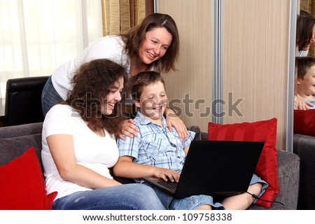 Happy mother with her children with a laptop - stock photo