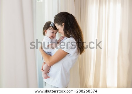 Happy mother with her cute baby girl at home - stock photo