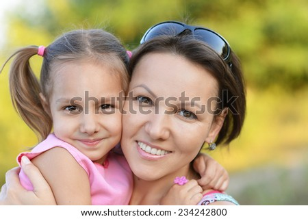 Happy mother with her cute daughter in autumn park - stock photo