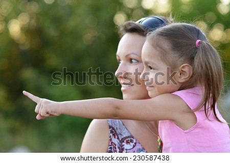 Happy mother with her cute daughter in autumn park, daughter is pointing on somewhere - stock photo