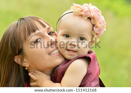 Happy mother with her cute daughter in summer park