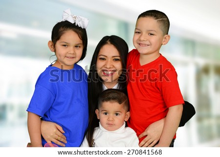 Happy mother with her daughter and two sons smiling at the camera - stock photo