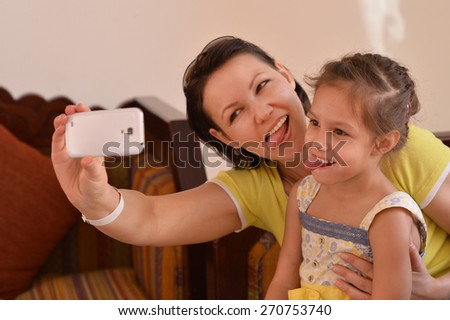 Happy mother with her daughter in summer park with phone - stock photo