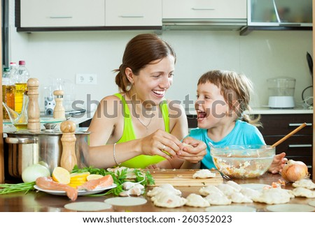 Happy mother with her daughter makes  fish meatballs in  home kitchen