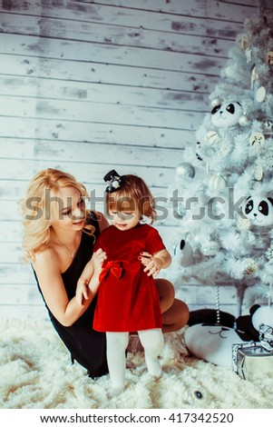 happy mother with her daughter near Christmas tree - stock photo