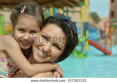 Happy mother with her daughter near pool at summer - stock photo