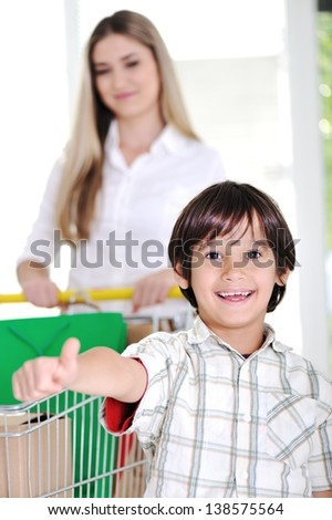Happy mother with her kid shopping using basket - stock photo